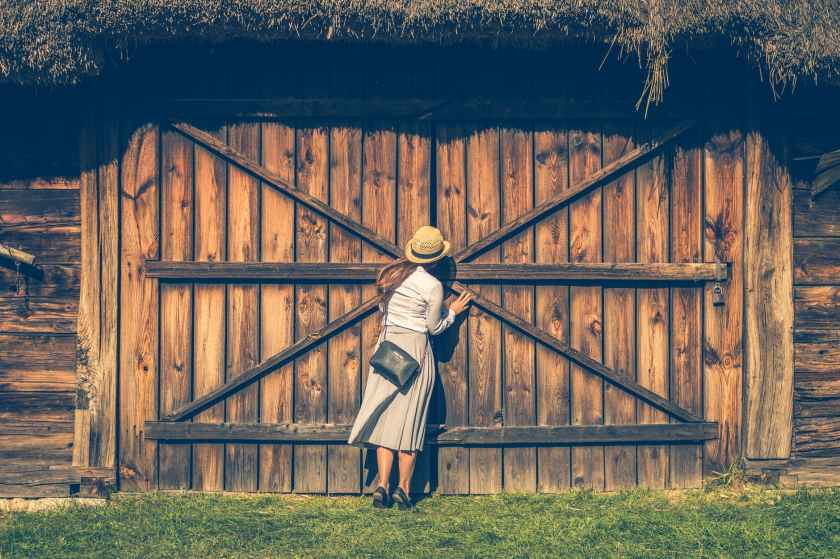 woman peaking on brown wooden gate